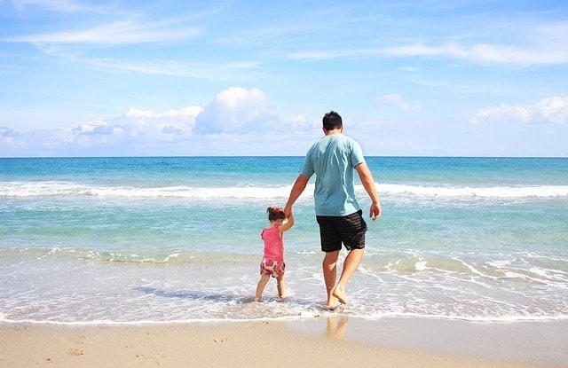 海辺で子供と戯れている男性