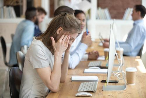 社内で悩む女性の画像